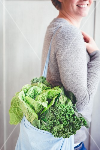 A woman carrying a shopping bag full of green vegetables