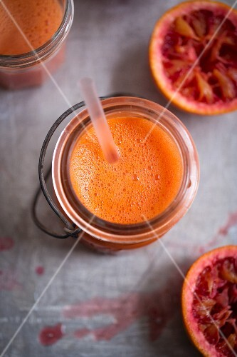 Blood orange smoothie in a glass jar with a straw