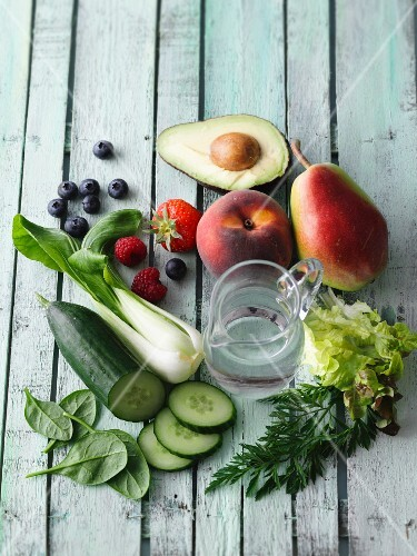 Ingredients for green smoothies on a wooden surface