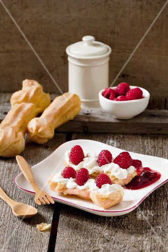 A halved eclair filled with cream and raspberries