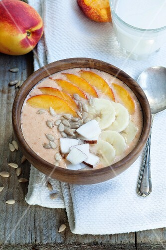 Smoothie bowl with peach, mango, banana, coconut and sunflower seeds