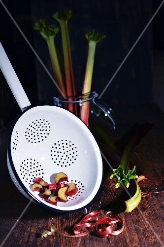 Pieces of rhubarb in a colander and a glass next to peeled rhubarb stems