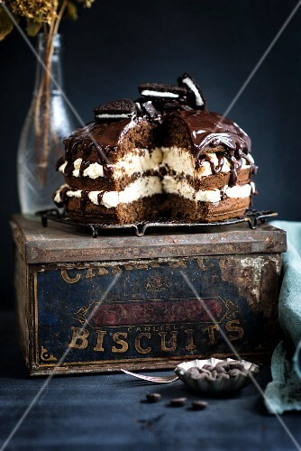 Chocolate cream cake with chocolate biscuits on an old biscuit tin