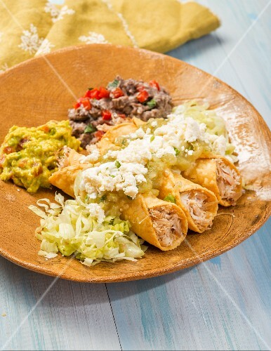 Taquitos with chicken, guacamole, queso fresco and bean purée (Mexico)