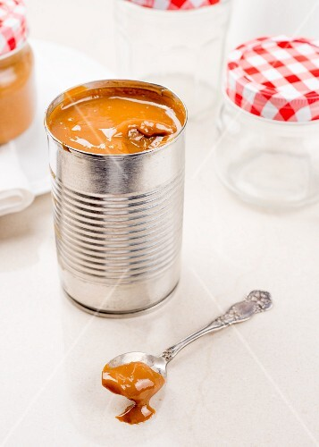 Dulce de leche in a tin and on a spoon