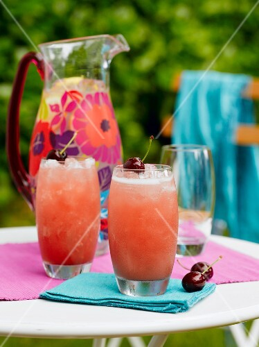 Two glasses of cherry apple gin fizz on a garden table