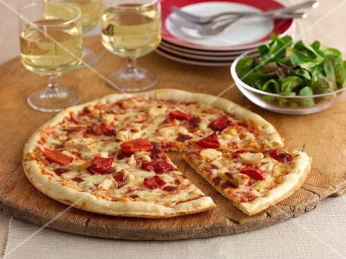 A chicken and red pepper pizza on a rustic board