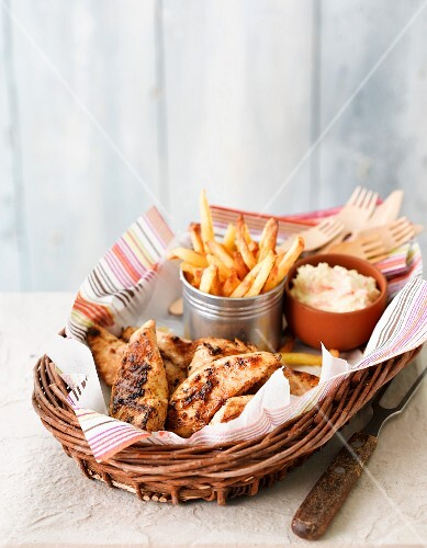Peri peri chicken with fries and coleslaw served in a basket