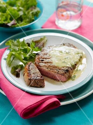 A sliced steak with salad and Bearnaise sauce
