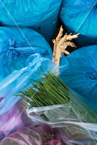 A chicken leg sticking out of full plastic bags with a large bunch of chives in the foreground