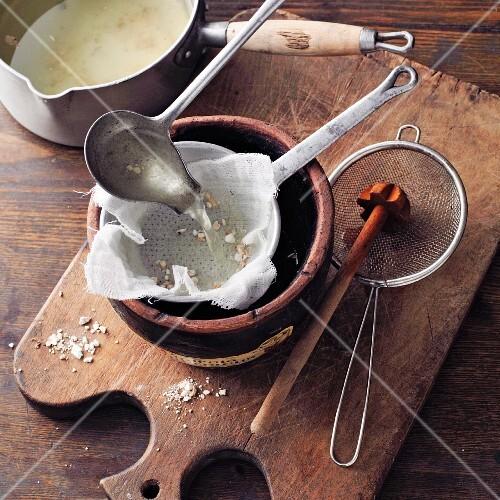 Arum elixir à la Hildegard von Bingen being made: wine being sieved