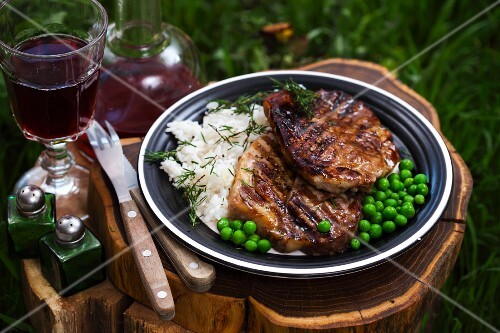 Grilled pork collar steak with rice and peas