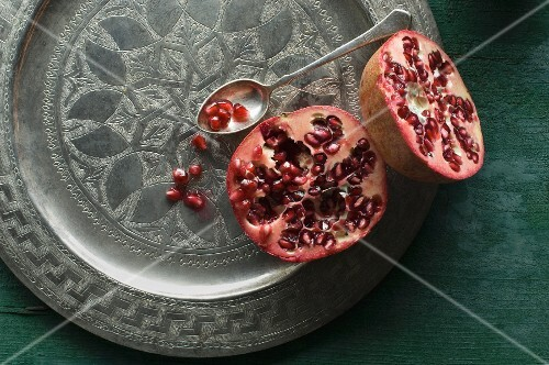 A halved pomegranate on a decorative metal plate