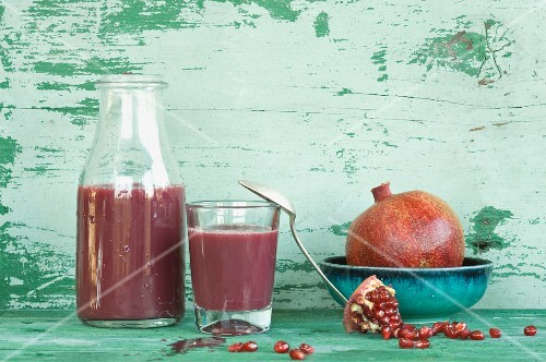An arrangement of pomegranates and pomegranate juice in a bottle and a glass