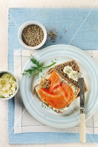 A slice of rye bread with salmon, butter and dill