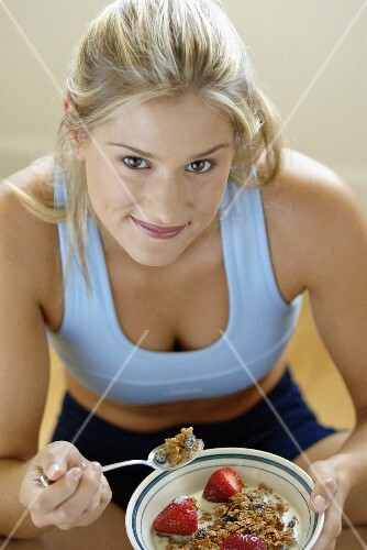 A young woman wearing sports clothes eating muesli with strawberries