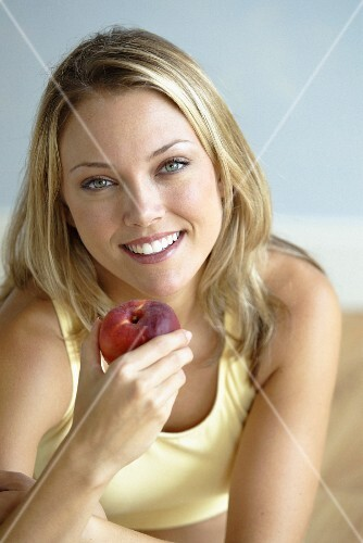 A young blonde woman wearing a tank top holding a nectarine