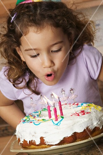A little girl blowing out birthday cake candles