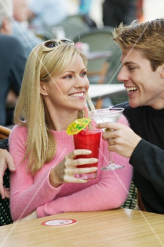 A young couple toasting with cocktails
