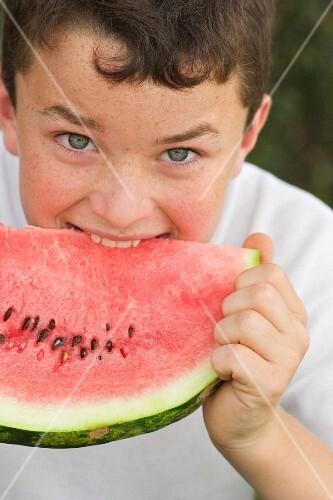 A boy biting into a watermelon