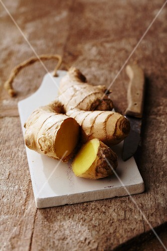 A ginger root on a wooden chopping board