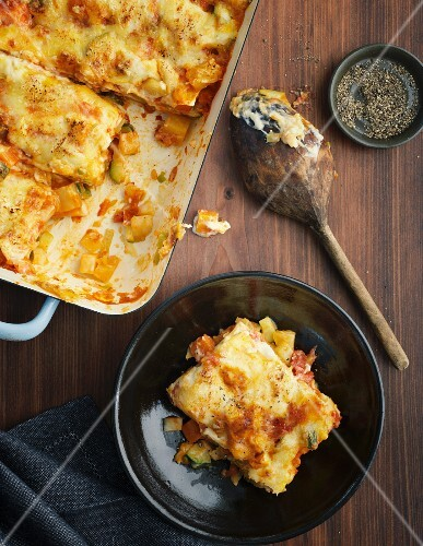 Vegetable lasagne in a baking dish and on a plate