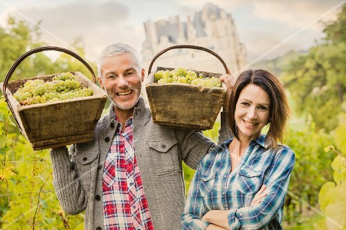 A man and a woman with wooden basket of freshly picked grapes