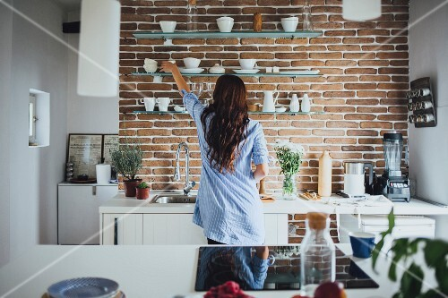 A woman in a kitchen in front of a crockery shelf