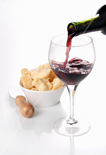 Red wine being poured into a glass with a bowl of Parmesan cheese in the background
