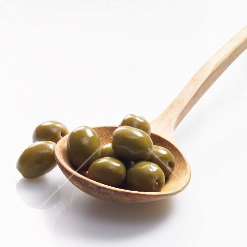 Green olives on a wooden spoon
