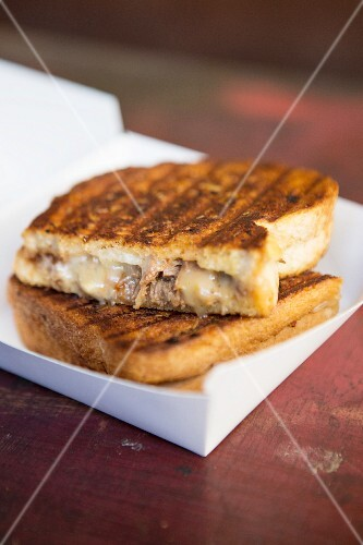 A toasted sandwich with meat and cheese
