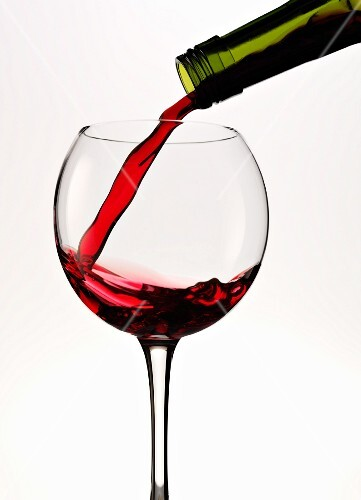 Red wine being poured into a round glass