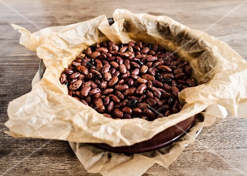 Shortcrust pastry in a red spring form pan covered with baking paper weighed down with beans