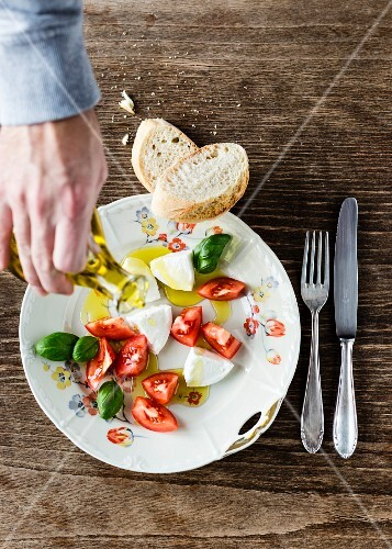 Olive oil being pored over mozzarella, tomato pieces, basil and baguette on an old floral patterned porcelain plate