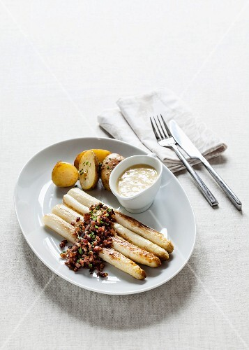 White asparagus with fried diced bacon, chives, Hollandaise sauce and potatoes