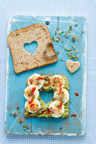 A slice of bread topped with guacamole, hard-boiled egg, bean sprouts and Sriracha sauce with a heart cut out in the middle