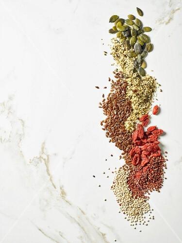 Pumpkin seeds, flax seeds, goji seeds, hemp seeds, white and red quinoa seeds (seen from above)