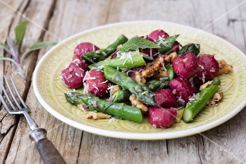 Beetroot gnocchi with green asparagus, walnuts and sage