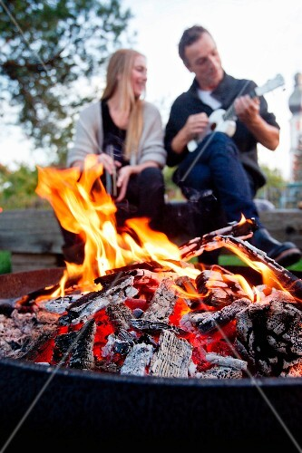 A blazing fire in a fire bowl with a young couple with a ukelele in the background