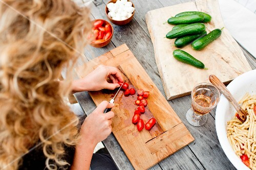 A woman slicing date tomatoes on a wooden chopping board