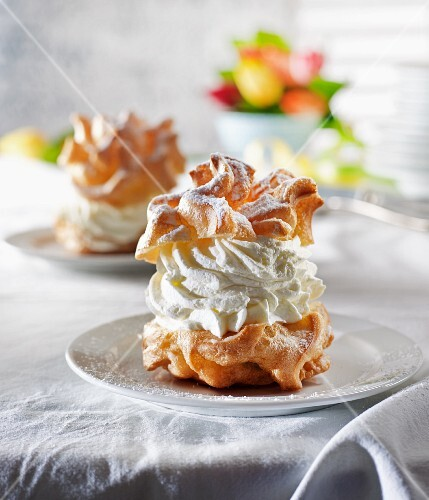 Profiterole with whipped cream and icing sugar