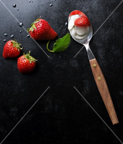 Fresh strawberries and yoghurt on a spoon
