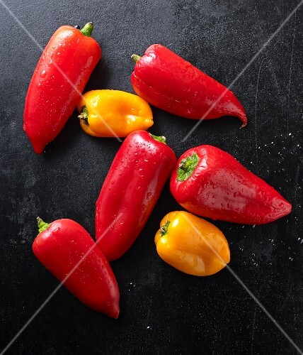 Fresh mini peppers on a black baking tray