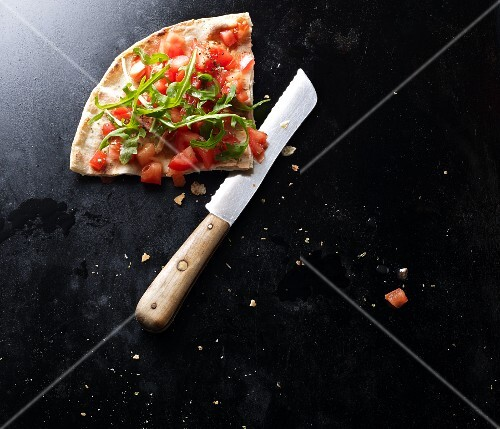 A slice of bruschetta pizza with a knife on a black baking tray