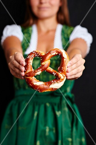 A woman wearing a Dirndl holding a pretzel