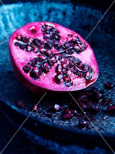 Half a pomegranate on a blue plate
