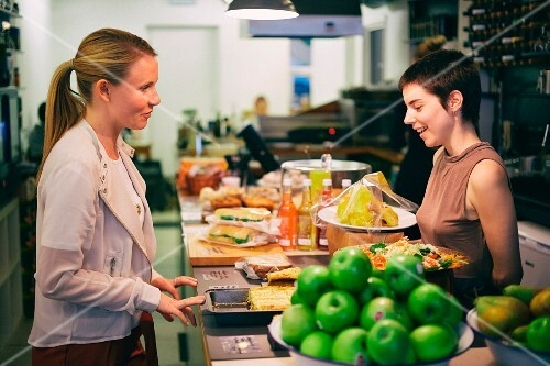 A waitress advising a customer at a counter in a cafe
