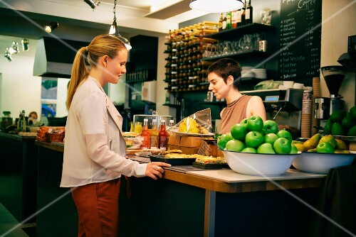 A waitress talking to a customer in a cafe