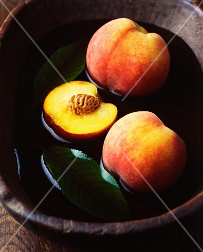 Whole and halved peaches with leaves in vintage wooden bowl of water