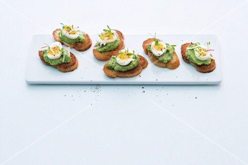Crostini topped with pea and avocado cream and quail's eggs